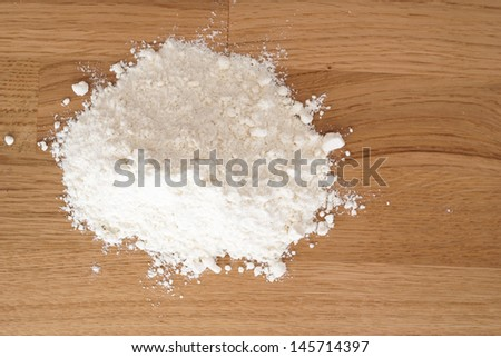 Flour heap on wooden background - stock photo