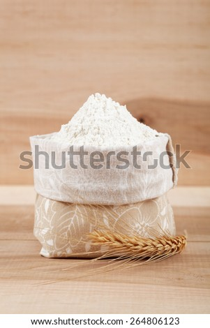 Flour in a canvas bag and ear of wheat on the wooden table. - stock photo