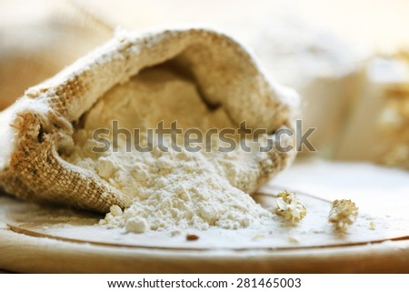 Flour in burlap bag on wooden cutting board and blurred background - stock photo