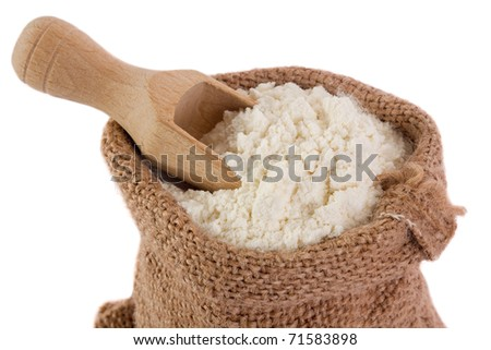 Flour in burlap sack and wooden spoon - stock photo
