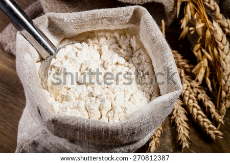 Flour in burlap sack with scoop of metal - stock photo