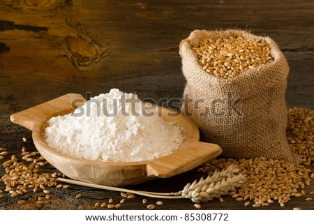 Flour in homemade wooden bowl and wheat in burlap bag - stock photo