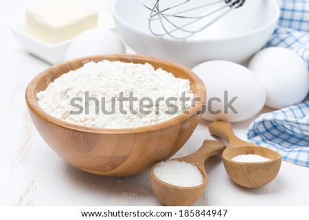flour, salt, sugar and eggs for baking pancakes on wooden table, horizontal - stock photo