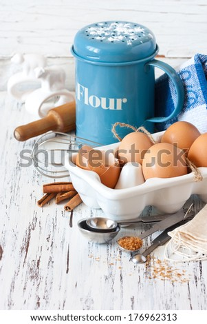 Flour strainer, wooden rolling pin, whisk, measuring spoons and food ingredients for baking on a white kitchen board. - stock photo