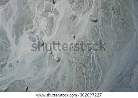 Flow of grit and soil in muddy stream in Alaska. - stock photo