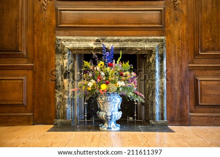 Flower arrangement of colorful summer blooms in a blue and white pottery urn in a historical marble fireplace with wood paneling on the walls - stock photo
