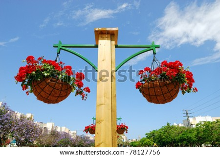 Flower basket on a post - stock photo