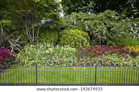 Flower bed and grass behind small fence - stock photo