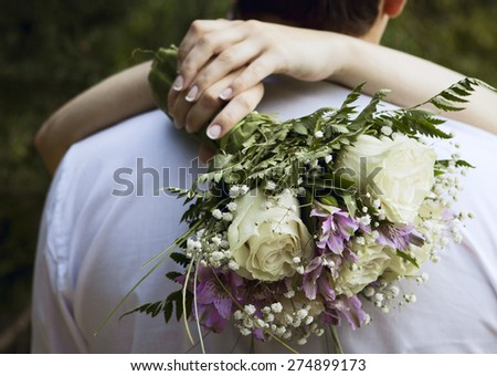 flower bouqet in hands of bride embracing groom - stock photo