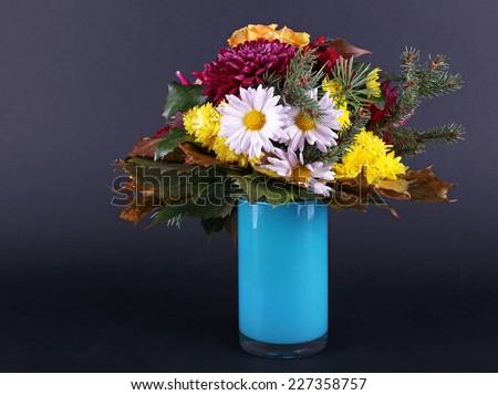 Flower bouquet in blue vase on dark grey background - stock photo