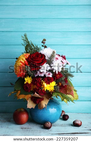 Flower bouquet in blue vase on table on blue wooden wall background - stock photo