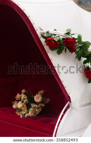 flower Bouquet on a red seat of a wedding carriage - stock photo