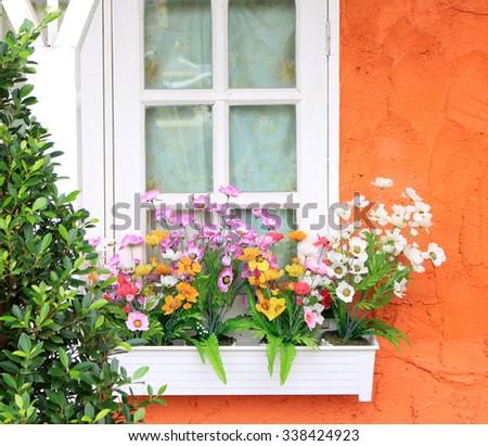 Flower box in window of orange building - stock photo