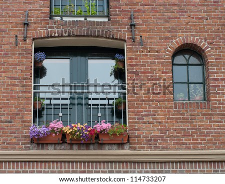 flower boxes with blooming flowers in a window in Groningen, Netherlands - stock photo