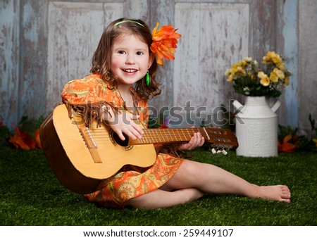 Flower Child.  Adorable preschooler dressed in retro 60's clothing, sitting on the grass, playing a guitar.  Slight motion blur on the hand that is strumming the guitar. - stock photo