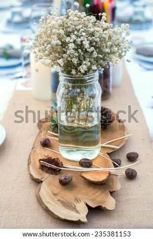 flower decoration in glass jar on dinning table - stock photo