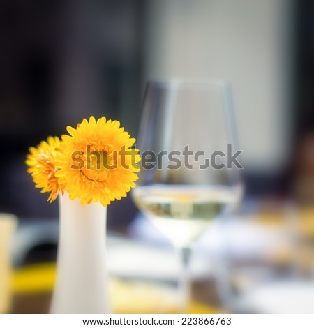 Flower decoration with a glass of white wine on the background.  Shallow DOF - stock photo