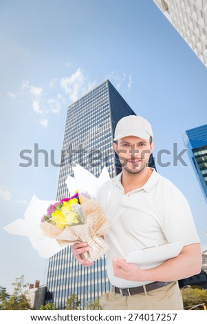 Flower delivery man showing clipboard against skyscraper - stock photo