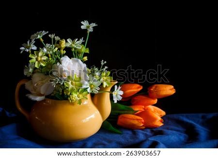 Flower in a yellow tea pot and orange tulip,cozy home rustic decor, cottage living, still life image dark tone - stock photo
