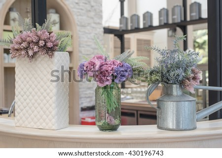 flower in different jar for decorating on coffee&tea bar counter, toned image - stock photo