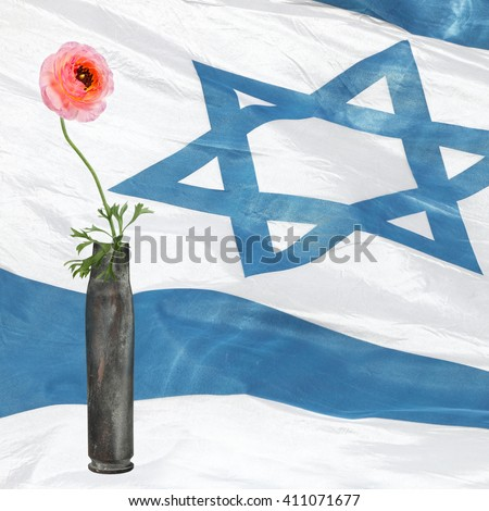 Flower in the cartridge case with Israeli national flag in blur background. Revival - stock photo