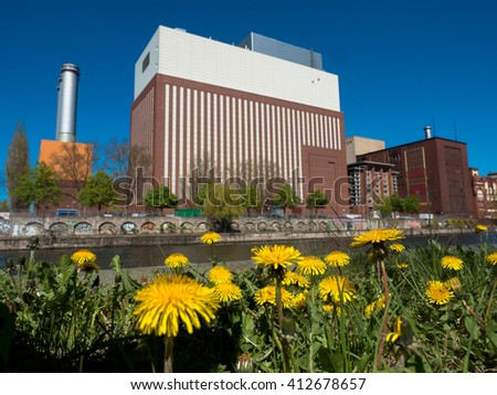 flower meadow in front of a power plant - stock photo
