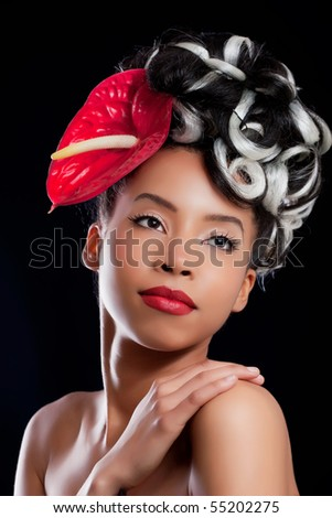 Flower pinup: beautiful young girl wearing a flower hat, isolated on black - stock photo