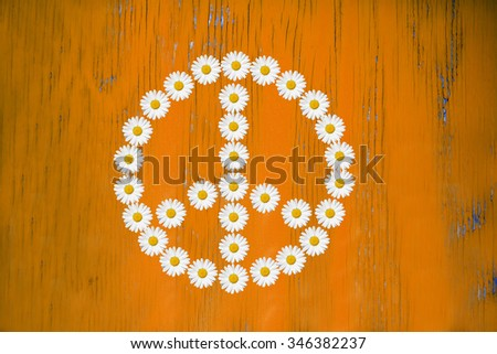 flower power sign made in daisy flower on wooden board - stock photo