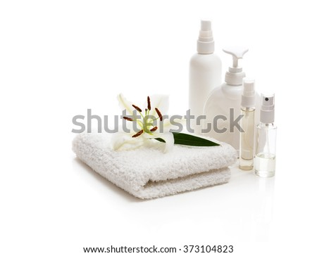 Flower white Lily lying on a towel and bottles - stock photo