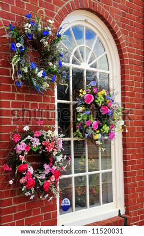 Flower wreaths displayed on a flower shop window - stock photo