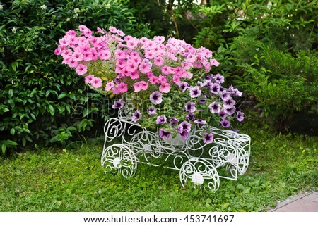 Flowerbed from forged openwork white metal with bright pink flowers. Decorative ironwork car with petunias. Modern garden decoration. - stock photo