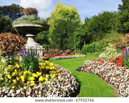 Flowerbeds, Grass Pathway and Ornamental Vase in a Formal Garden - stock photo