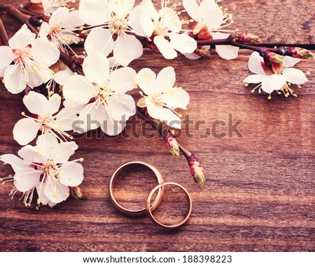 Flowering branch with white delicate flowers on wooden surface. Declaration of love, spring. Wedding card, Valentine's Day greeting. Wedding rings. Wedding bouquet, background. Empty wooden tabletop  - stock photo