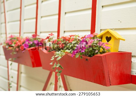 Flowers and a yellow bird house in bright red planters mounted on the side of a white and red building.  - stock photo