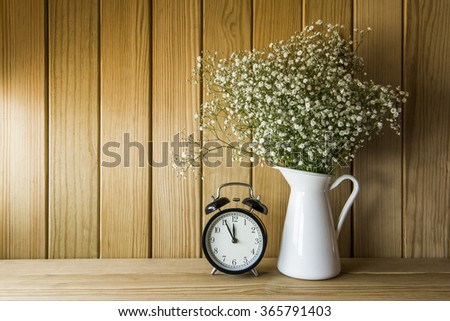 flowers and alarm clock on a wooden wall shelf - stock photo