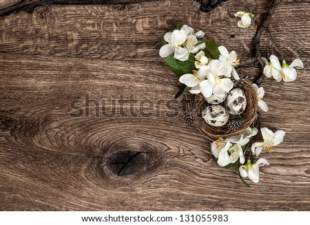 flowers and easter nest with eggs on rustic wooden background. spring apple tree blossom - stock photo
