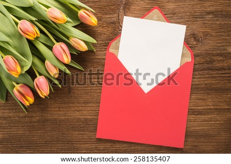 Flowers and envelope on wooden background   - stock photo