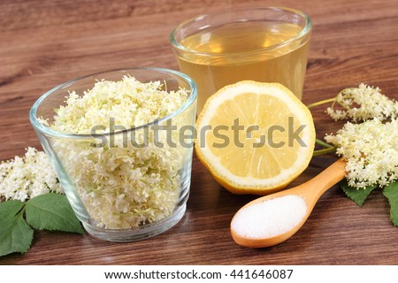 Flowers and fresh healthy juice of elderberry and ingredients for preparing beverage on rustic board, alternative medicine and therapy - stock photo