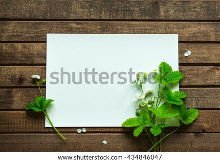 Flowers and leaves of wild strawberry with blank paper for greeting message on wooden background. Vintage Floral mock up with white flowers. Copy space - stock photo
