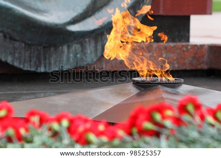 Flowers at memorial to tomb of Unknown Soldier in Alexander Garden at Victory Day; Eternal Flame - stock photo