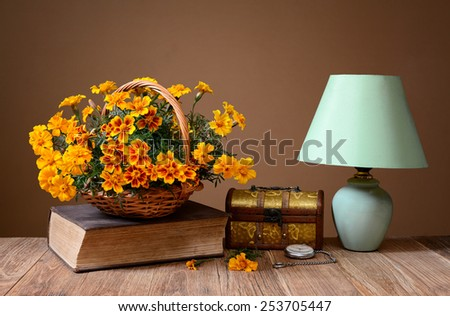 Flowers, books, jewelry box and table lamp on the table - stock photo