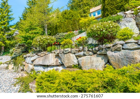 Flowers, bushes and stones in front of the house, front yard. Landscape design. - stock photo