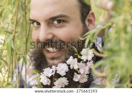 Flowers decorate the beard of this young man enjoying nature - stock photo