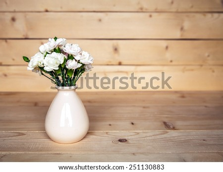flowers. delicate bouquet of carnations in vintage vase with heart on wooden background. Valentine's Day - stock photo
