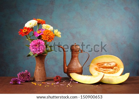 Flowers in a vase and fresh sliced cantaloupe - stock photo
