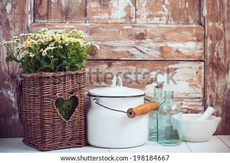 Flowers in a wicker basket, glass bottles and vintage milk can on wooden background, cozy home rustic decor, cottage living - stock photo