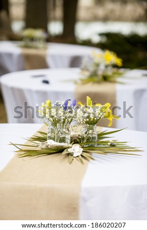 flowers in mason jars on tables for reception - stock photo