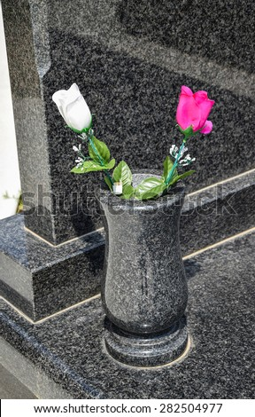 Flowers in the vase next to a tombstone in the cemetery - stock photo