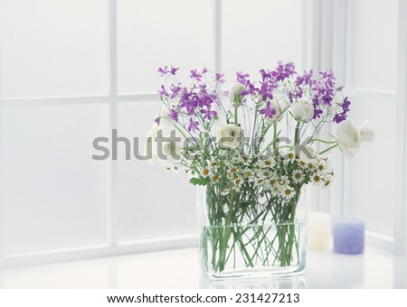 flowers in vase at the table - stock photo