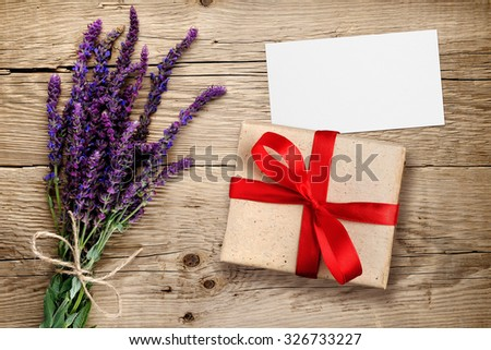 Flowers of salvia and gift box with visiting card on wooden background - stock photo